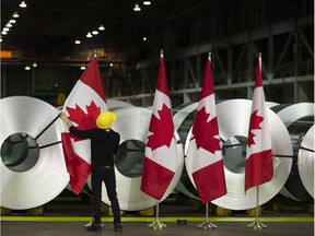 A worker straightens Canadian flags in front of rolls of coated steel before a visit by Foreign Affairs Minister Chrystia Freeland in Hamilton, Ont., on Friday, June 29, 2018. Freeland met with employees in the cold rolling plant and announced the government's latest efforts in response to U.S. tariffs on Canadian steel and aluminum.