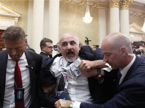 A man is shoved out of the room after showing prior to a press conference after the meeting of U.S. President Donald Trump and Russian President Vladimir Putin at the Presidential Palace in Helsinki, Finland, Monday, July 16, 2018.