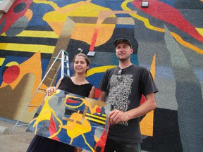 Calgary mural team Nasarimba hold their sketch upside down for a laugh in front of their 107 Avenue mural.