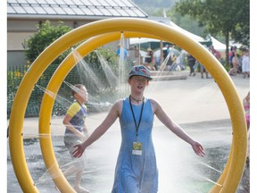 Mariah Fournier walks through the  spray park to cool down in temperatures topping out at 34 C at the Edmonton Folk Music Festival site in Gallagher Park on Thursday, Aug. 9, 2018.
