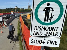A new sign has gone up indicating a $100 fine for cyclists riding over on the narrow shared sidewalk lane over the Groat Road Bridge which is under construction in Edmonton on Thursday, Sept. 6, 2018.