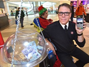 Maj. Al Hoeft of the Salvation Army Kettle Campaign holds one of 15 point of sale terminals that are now accepting donations by debit and credit card. Volunteer Shannon Kidner, back, is ringing the bells in City Centre Mall on Monday, Nov. 26, 2018 in the campaign that goes until Dec. 24 with a goal of raising $550,000 in Edmonton.