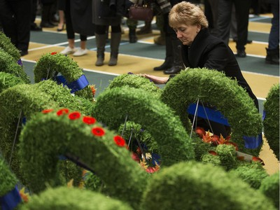 A woman gently touches a wreath while paying respects during the Remembrance Day Service at the University of Alberta's Van Vliet Centre, in Edmonton Sunday Nov. 11, 2018.