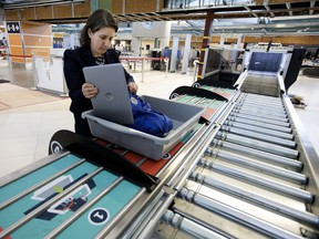 Canadian Air Transport Security Authority (CATSA) spokeswoman Christine Langlois demonstrates the new CATSA Plus security screening system at the Edmonton international Airport in Edmonton on Friday, Dec. 7, 2018. The new system allows four passengers to load their carry-on baggage for security screening at the same time.