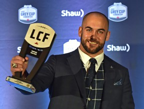 Edmonton Eskimos snapper Ryan King holds up his Tom Pate Memorial Award for contribution to his team, community and outstanding sportsmanship at the CFL Awards Gala in Edmonton on Nov. 22, 2018.
