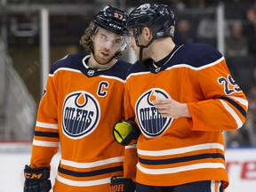 Edmonton Oilers star Connor McDavid, left, talks to teammate  Leon Draisaitl during NHL action against the Carolina Hurricanes at Rogers Place on Jan. 20, 2019.