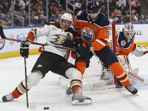 Anaheim Ducks forward Corey Perry (10) and Edmonton Oilers defenceman Adam Larsson (6) battle for the puck during third period NHL action at Rogers Place on Saturday February 23, 2019.