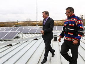 Minister of Indigenous Relations Richard Feehan, left, speaks with Montana First Nation Councillor Brad Rabbit while inspecting the solar panel installation of the roof of the band's administrative building in 2016. The minister was visiting Maskwacis to announce the launch two programs that provided $2.5 million for First Nations and Metis Settlements to undertake renewable energy projects and energy efficiency audits in their communities.