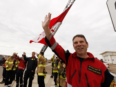 High Level firefighters welcome residents home with a giant Canadian flag on their return to High Level, Alberta, after being evacuated due to the Chuckegg Creek wildfire on Monday, June 3, 2019.
