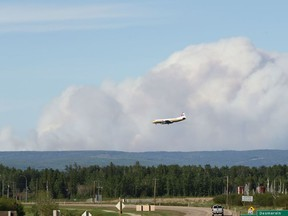 The McMillan Complex wildfires are seen burning from Slave Lake, Alberta as an air tanker lands on June 2, 2019. Photo by Ian Kucerak