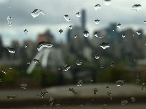 Rain drops on a window with city skyline in back, as the off and on again showers continue in Edmonton, June 24, 2019.