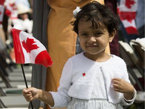 A young girl watches the Canada Day citizenship ceremony at the Alberta Legislature, in Edmonton Sunday July 1, 2018.
