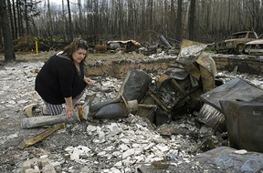 Paddle Prairie Metis Settlement resident Wilma Cardinal sifts through the remains of her sister-in-law's home on Wednesday June 19, 2019. A wildfire destroyed at least fifteen homes on the settlement, located 80 kilometres south of High Level, Alberta. All residents of the largest Metis settlement in Alberta have been evacuated but are expected to return this week.  Wildfires in northern Alberta are still burning out of control.