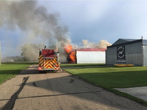 Fire crews battle a blaze that broke out in a private hanger at the Lacombe Regional Airport on the evening of July 7, 2019. The fire destroyed three small planes.