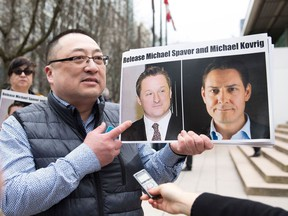 In this file photo taken on March 6, 2019, Louis Huang of Vancouver Freedom and Democracy for China holds photos of Canadians Michael Spavor and Michael Kovrig, who are being detained by China, in Vancouver, Canada.