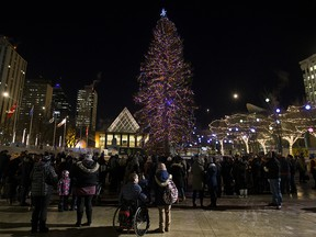 A small crowd gathers to watch the official light up of the Downtown Business Association's Christmas Tree in Churchill Square, in Edmonton on Nov. 16, 2018.