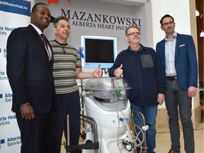 Doctors Jayan Nagendran, left, and Darren Freed, right, inventors of the Organ Support System (EVOSS) pose with lung transplant recipients Ron Kruse, second from right, and Ron Schaworski as the University Hospital Foundation celebrates 12 successful lung transplants using the Ex-Vivo (EVOSS) device, at the Mazankowski Alberta Heart Institute in Edmonton, Thursday, Nov. 7, 2019.