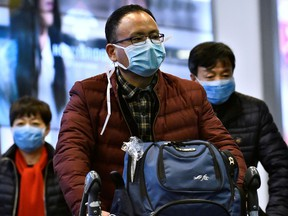A traveller wears a mask, after arriving on a direct flight from China at Vancouver International Airport in Richmond, B.C., Jan. 24, 2020.