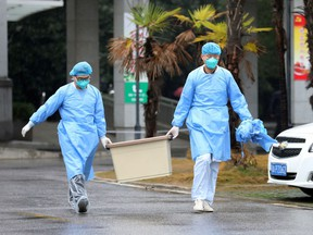 Medical staff carry a box as they walk at the Jinyintan hospital, where patients with pneumonia caused by a new strain of coronavirus are being treated, in Wuhan, Hubei province, China, on Jan. 10, 2020.