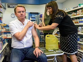 Alberta Health Minister Tyler Shandro, receiving a flu shot from a pharmacist in October, has proposed health-care policy changes that could amount to rationing of access to your doctor, says columnist Danielle Smith.