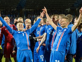 Iceland's players including Iceland's forward Johann Berg Gudmundsson (L) and Iceland's forward Alfred Finnbogason celebrate after the FIFA World Cup 2018 qualification football match between Iceland and Kosovo in Reykjavik, Iceland on October 9, 2017. Iceland qualified for the FIFA World Cup 2018 as smallest country ever after beating Kosovo 2-0 at home in Reykjavik.