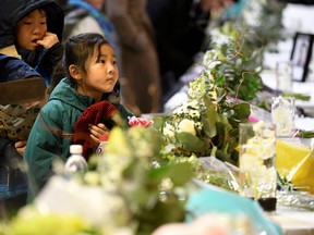 Flowers and photos of the victims set up at a memorial service at the University of Alberta for the victims of a Ukrainian passenger plane that crashed in Iran, in Edmonton, Alberta, Canada January 12, 2020.