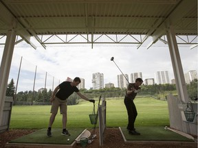 Golfers hit the driving range on a rainy afternoon at Victoria Golf Course in Edmonton.
