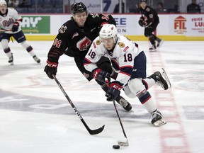 Regina Pats forward Cole Dubinsky tries to get past Calder Anderson of the Moose Jaw Warriors in WHL action at the Brandt Centre on Tuesday.