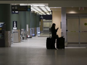A passenger waits in the arrivals area at the Edmonton International Airport on Monday, March 16, 2020, in Edmonton.