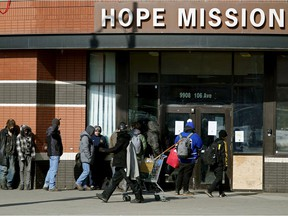 People lined up outside the Hope Mission in Edmonton on March 19, 2020 during the global COVID-19 pandemic.