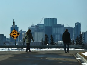 Two people keeping their distance while out for a walk along Ada Blvd. in Edmonton, April 6, 2020.