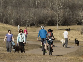 Cyclists and dog walkers meet in a warm spring afternoon in Dawson Park in Edmonton, on Monday, April 23, 2018.