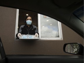 An employee at the 7455 101 Avenue A&W location poses for a photo with packages of non-medical masks in the restaurant's drive-thru, in Edmonton Monday June 8, 2020. In an effort to prevent the spread of COVID-19 the Province is distributing 20 million free, non-medical face masks through A&W, McDonald's, and Tim Hortons drive-thrus. Photo by David Bloom