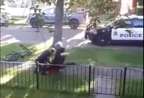 An Edmonton police officer is seen jumping with his knee onto a man lying on the ground during a 2019 arrest.