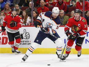 Edmonton Oilers left wing James Neal (18) looks to control the puck against Chicago Blackhawks center Jonathan Toews (19) during the first period at United Center on Monday, Oct. 14, 2019.