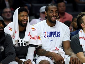 Paul George, left, and Kawhi Leonard of the L.A. Clippers laugh on the bench during a 120-99 win over the Phoenix Suns at Staples Center on Dec. 17, 2019 in Los Angeles, Calif.