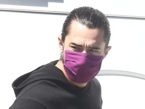 Calgary Flames forward Johnny Gaudreau is masked as the team leaves the Saddledome on buses in Calgary on July 26, 2020.