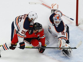 Edmonton Oilers defencemen Darnell Nurse (25) shoves Chicago Blackhawks forward Jonathan Toews (19) into Edmonton Oilers goaltender Mikko Koskinen (19) during the first period in the Western Conference qualifications at Rogers Place on Friday, Aug. 8, 2020.
