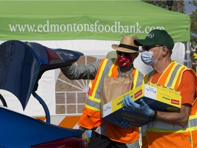 Volunteers unload donations during the Edmonton Food Banks' drive thru Heritage Food Drive in the Southgate Centre mall parking lot, in Edmonton Saturday Aug. 1, 2020. Traditionally the Edmonton Food Bank would be collecting donations at the Heritage Festival.