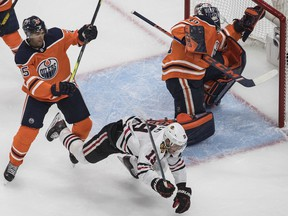 Edmonton Oilers' Darnell Nurse checks Chicago Blackhawks' Jonathan Toews as goalie Mike Smith makes the save during first period NHL playoff action in Edmonton, Aug. 1, 2020.