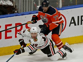 Chicago Black Hawks Jonathan Toews (left) is checked by Edmonton Oilers Oscar Klefbom during NHL hockey game action in Edmonton on Tuesday February 11, 2020.
