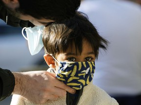 A father helps his young son put on a face mask before entering a shop in Edmonton during the coronavirus pandemic on Friday September 11, 2020.