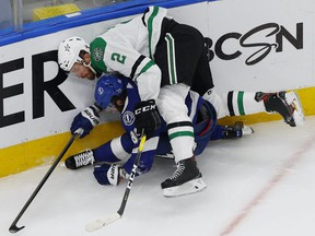 Tampa Bay Lightning right wing Nikita Kucherov (86) is checked by Dallas Stars defenseman Jamie Oleksiak (2) during the third period in game one of the 2020 Stanley Cup Final at Rogers Place on Sept. 19, 2020.