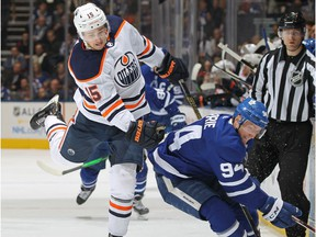 Josh Archibald (15) of the Edmonton Oilers side steps a hit from Tyson Barrie (94) of the Toronto Maple Leafs during an NHL game at Scotiabank Arena on Jan. 6, 2020, in Toronto.