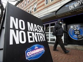 A pedestrian wearing a mask to protect against COVID-19 makes their way past the Commercial Hotel - Blues On Whyte Pub, 10329 82 Ave., in Edmonton Tuesday Nov. 24, 2020.