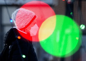 A pedestrian wearing a face mask walks past the Christmas lights in Dr. Wilbert McIntyre Park, 8331 104 St., in Edmonton Sunday Dec. 20, 2020.