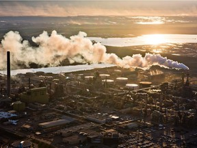 The setting sun reflects off a tailings pond behind Syncrude's oilsands upgrading facility north of Fort McMurray, Alta. File photo.