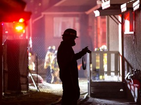 An Edmonton Fire Rescue Service investigator takes photos as firefighters extinguish a fire in a home on 95 Street near 111 Avenue in Edmonton, on Wednesday, Jan. 20, 2021.