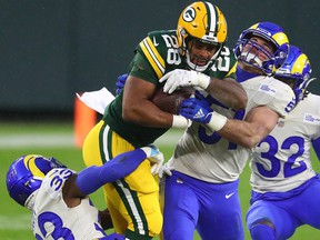 Green Bay Packers running back AJ Dillon (28) runs with the ball while Los Angeles Rams safety Nick Scott (33) and linebacker Troy Reeder (51) attempt to tackle him on Jan. 16, 2021, at Lambeau Field.