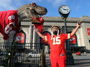 A Kansas City Chiefs fan in a full Native American headdress poses in front of a dinosaur statue clothed in a Kansas City Chiefs jersey as a Tampa Bay Buccaneer effigy dangles from his mouth, outside of Union Station in downtown Kansas City ahead of Super Bowl LV on Feb. 01, 2021 in Kansas City, Mi.